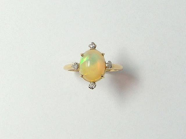 Bague en or, ornée d'une opale cabochon en serti griffe, encadrée de diamants taille ancienne. (égrisures). Poids brut: 2.90 g. TDD: 52.