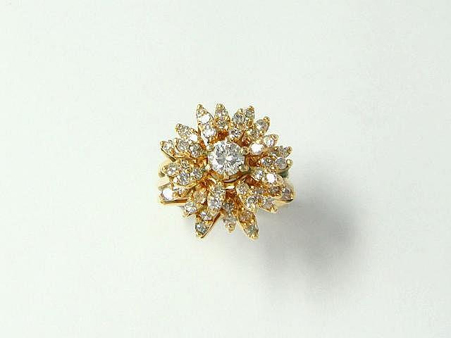 Bague en or 14 k, stylisant une fleur, ornée de diamants brillantés dont un plus important au centre. (égrisures). Poids brut: 8.40 g. TDD: 50.