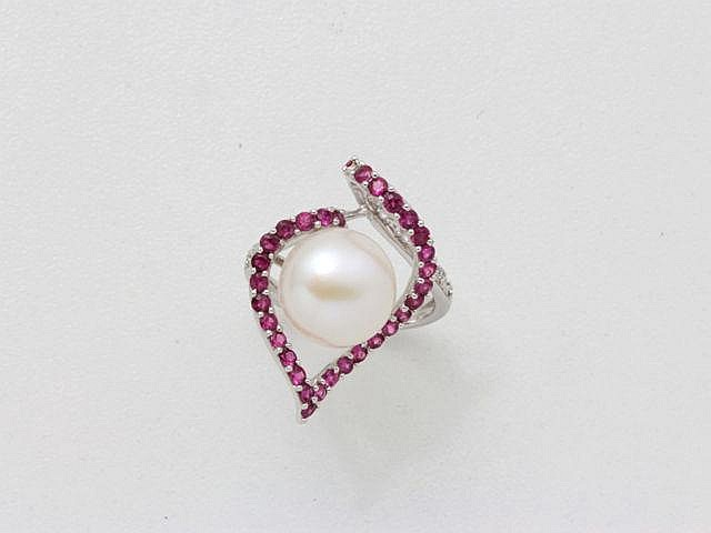 Bague en or gris, ornée d'une perle de culture bouton d'environ 11 mm, rehaussée de rubis ronds facettés et de diamants brillantés.. Poids brut: 5.60 g. TDD: 52. (manque)