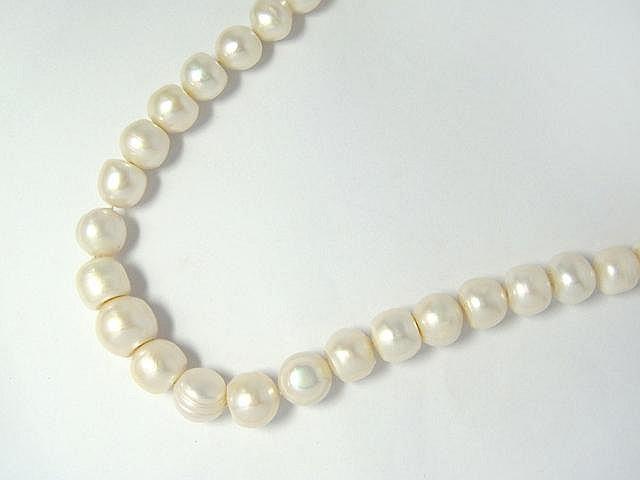 Collier composé d'un rang de perles de culture d'eau douce blanches baroques d'environ 10.5 à 14.2 mm, agrémenté d'un fermoir à cliquet invisible en métal.. Long: 47 cm.