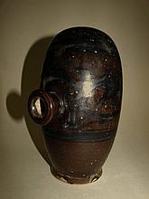 Récipient cizhu à alcool de riz de forme ovoïde à base plate ouvert par un goulot latéral d' où se fixait le système d'écoulement. Grès porcelaineux à couverte monochrome brune décoré en noir de motifs géométriques. Chine. Dynastie Yuan. 1271 à 1368.