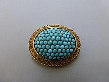 A decorative gold and turquoise brooch, unmarked.