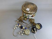A silver lidded pot with a small quantity of
