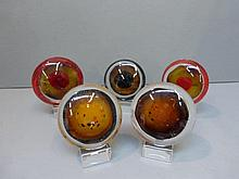 Five glass paperweights.