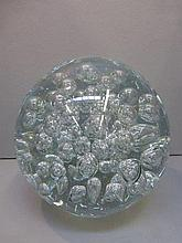 A large bubble glass paperweight.