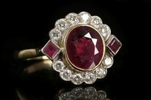 An 18ct gold, ruby and diamond set cluster ring, with central collet set oval faceted stone, flanked by princess cut rubies over shoulders and framed by brilliant round cut diamonds.  Main ruby: 1.80ct approx est.  Total Diamond Weight Estimate: 0.36ct
