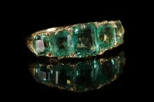 A Victorian style high carat gold and graduated five stone emerald ring, the stones framed by diamond set claws over a scroll engraved gallery.  Emerald: 3.95ct total est.  Size: NV.
