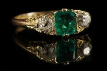 A Victorian 18ct gold, emerald and diamond three stone ring, with scroll work gallery.  Emerald: 0.93ct.  Diamond: 0.80ct total est.  Size: U½.