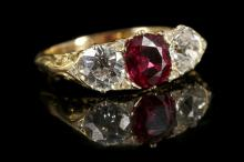 An 18ct gold, ruby and diamond set three stone ring, with pierced scroll work gallery.  Ruby: Thailand, no heat, 1.13ct.  Diamond: 1.60ct total est.  Size: P.  GCS ruby certificate.