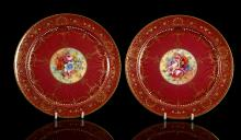 A PAIR OF ROYAL WORCESTER CABINET PLATES BY ERNEST BARKER, dated 1937, both finely painted with a spray of colourful flowers, the rims elaborately gilded and jewelled with white, yellow and green enamels on a crimson ground, 26.5cm diameter, printed factory marks in puce, retailed by Asprey's (2)