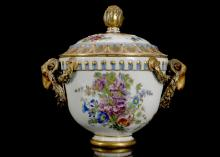 A MARCOLINI MEISSEN BOWL AND COVER, late 18th century, with ram's head terminals hung with garlands of flowers picked out in gold, painted with sprigs and sprays of scattered flowers, the rim with a neoclassical border, the similarly decorated cover with a formal border and acanthus flower knop, 16cm high, crossed swords and star mark in blue (restored)