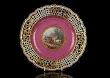 A FINE MEISSEN CABINET PLATE, circa 1870, the centre finely painted with a tavern scene of men drinking beer around a table, reserved within gilt floral and scrollwork borders on a puce ground, the elaborately pierced rim applied with forget-me-nots and foliage picked out in blue and gold alternating with lattice panels, the reverse with a formal gilt border,25cm diameter, crossed swords mark in underglaze blue, incised numerals (restored)   FOOTNOTES: Pair to the previous lot.