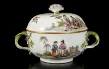 A MEISSEN TWIN-HANDLED ECUELLE AND COVER, circa 1750, finely painted to both sides with rural landscape scenes depicting Watteauesque peasant figures, the entwined crabstock handles tied with pink ribbons and with flowering branch terminals, the cover with a large flower finial, 13.5cm high, crossed swords mark in underglaze blue