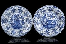 A PAIR OF CHINESE BLUE AND WHITE 'PHOENIX ON ROCKS' PLATES. Qing Dynasty, Kangxi era. Each decorated with a roundel enclosing a bird on a rocky base, below flowering branches, the moulded scalloped rim with a band of lappets enclosing, 27cm diameter.