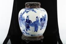 A CHINESE BLUE AND WHITE GINGER JAR WITH FIGURATIVE SCENE.   Late Qing Dynasty, 19th Century.   Decorated with a continuous scene of figures in a landscape, wooden stand and reticulated wooden cover, 25.5cm H.   ??? ???????