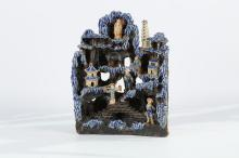 A SHIWAN BLUE GLAZED MOUNTAIN LANDSCAPE GROTTO.   Late Qing Dynasty, 19th Century.   Featuring figures and buildings in various registers within a rocky and pine-filled landscape, 32cm H.