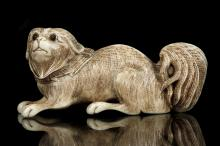 A JAPANESE CARVED IVORY FIGURE OF A PUPPY.   19th Century.   7cm long.