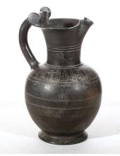 AN ETRUSCAN BUCCHERO WARE OINOCHOE   Circa 6th Century B.C. With trefoil lip, slightly squat round body and handle with round cross-section joining the flaring rim with two rotellae, decorated with incised bands on the body and neck, a band of tongues on the shoulder terminating with scrolls either side of the handle, 34.2cm high   Provenance: English deceased estate of a dentist, acquired in the 1990s.
