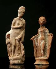 TWO ROMAN TERRACOTTA FIGURES OF APHRODITE   Circa 1st-2nd Century A.D. One depicted nude bringing her right arm to her breast, flanked by an Eros, 21.5cm high; the other holding drapery with both her hands, 18cm high (2)  Provenance: Alexandre Nicolai (1865-1952) Collection, Bordeaux, France. Thence by descent.