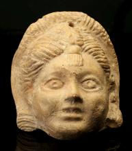 A ROMAN TERRACOTTA HOLLOW-BACKED MASK   Circa 1st-2nd Century A.D. Possibly representing a new Comedy courtesan or Hetaira, with centrally-parted hair and wearing a forehead tassle, pierced at the top for suspension, 13cm high   Provenance: Marcus Brooke (1923-2015) Collection, Glasgow, formed in the 1960s-1970s.