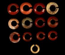 THIRTEEN EGYPTIAN HARDSTONE EARRINGS OR HAIR RINGS  New Kingdom, circa 1550-1070 B.C.  Of red jasper, carnelian, green stone and aragonite, a single penannular hoop with convex outer edge, 12mm-17mm external diam (13)  Provenance: Horatio and Patsy Melas Collection, Alexandria, Egypt, acquired before 1967. Thence by descent, moved to Switzerland and London.