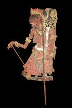 A 'WAYANG KULIT' SHADOW PUPPET, INDONESIA  Probably from Bali, depicting an old female character, topless, wearing a long skirt and jewellery, with elaborate cut-out details, articulated arm and two wood rods for moving, 59cm high