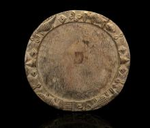 A YORUBA 'OPON IFA' DIVINATION TRAY, NIGERIA   Round, the wide raised border carved with two stylised eyes and mouth of the god Eshu, flanked by crocodiles, 38cm diam