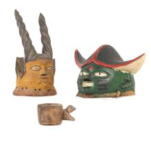 TWO YORUBA 'GELEDE' HELMET MASKS, NIGERIA  One with green face and pointed hat, 20cm high; another with yellow face, pointed ears and straight impala horns, 37cm high; together with a Zulu iron spear, the shaft cut off and mounted, 80cm high; and a wood cup with the handle as a stylised bird, dark brown patina, 8cm high (4)
