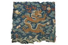 A CHINESE KESI ?DRAGON? TEXTILE FRAGMENT.     Early Qing Dynasty.     Depicting a five-clawed dragon among flames and clouds above foaming waves on a lapis blue ground, 38 x 40cm.      ?? ??????