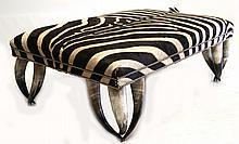 A LARGE MODERN OTTOMAN - with zebra pattern black and white striped hide top with studded detail, raised on legs formed from three cow horns, (85 x 85cm)
