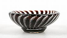 EDVIN OHRSTROM FOR ORREFORS - an early 20th century 'Ariel' art glass bowl, circa 1930, the design first developed by Vicke Lindstand, internally decorated with red swirling stripes, in clear cased glass, engraved signature with maker's marks under, pattern number 1711 E, (12.5cm diam)