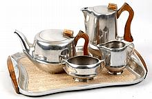 PICQUOT WARE - a 1950's aluminium tea/coffee set, consiting of tea pot, coffee pot, milk jug, sugar bowl, with sycamore wood handles, and matching tray, with shaped gallery, pattered formica base, and sycamore wood handles, engraved with maker's marks under, (tray; 43 x 28cm)