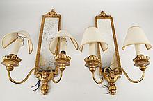 A pair of twin arm girondel wall lights, leaf surmount, ribbon fold trim, clouded mirror, 55cm high.