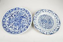Two Chinese Qing dynasty, blue and white dishes, one attractively decorated with a Buddhist lion dog and pups, the other with scrolling floral decoration, 30cm diameter.