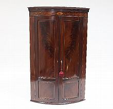 An early 19th Century mahogany bowfront corner cupboard, with dentil cornice and shell panelled and box strung frieze above two double panelled doors, 117cm x 74cm