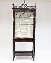 A Chippendale style Edwardian mahogany display cabinet, with fretwork cornice above a glazed door on a stand with blind fret rail and legs with tray stretcher, 200cm x 76cm