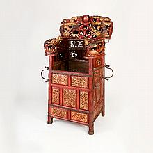 A Chinese hardwood throne chair, painted all over in red and gilded lacquer, the canopy and arms finely carved dragons with central flaming pearl, the front and sides set seven panels of geometric design, the back set an assortment of pierced and
