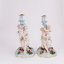 A pair of German porcelain figural candlesticks, late 19th Century, each modelled with a maiden and
