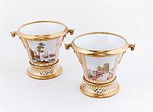 A pair of French porcelain cache-pots, painted with seaside landscapes reserved on a gilt-stripe gro