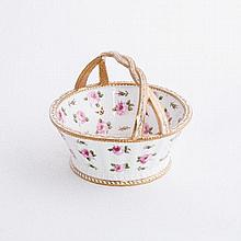 A porcelain circular basket, painted with pink roses in full bloom and bud, butterflies to the inter