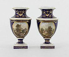 Two Derby topographical urn shaped vases, early 19th Century, each painted to the front with buildin