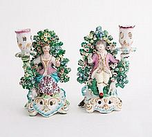 A pair of Derby figural candlesticks, modelled as a shepherd and shepherdess before bocage, circa 17