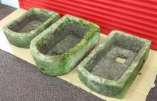 Three stone troughs, each with one rounded end, the largest 65cm long