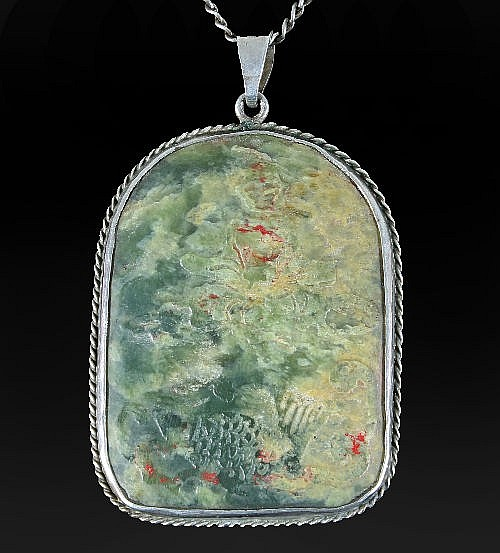 A Chinese carved jade type pendant carved with a