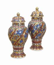 A PAIR OF 'CLOBBERED' CHINESE BLUE AND WHITE VASES AND COVERS,