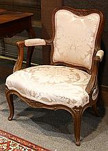 Louis XV walnut fauteuil en cabriolet, circa 1750, having a floral carved crest above the salmon upholstered seat and back, and risi...