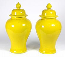 Pair of lidded porcelain urns in the Asian taste, executed in Chinese yellow, having lids with lotus form finials above classical ur...