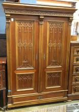 Gothic Revival style armoire, 19th century, having a molded and carved cornice above two paneled doors with applied Gothic tracery, ...