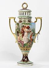 Royal Vienna style painted porcelain lidded urn, having  a gilt wreath finial above gilt handles flanking a central reserve  depicti...