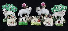 (lot of 9) Staffordshire figures of sheep, comprising a pair of ram and ewe spill vases, a pair of modern lambs with bocage, and thr...